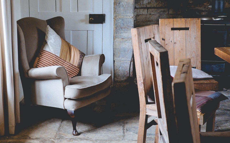 Woonkamer met een grijze stoel en een geblokte kussen. Je ziet nog net een tafel met daaraan 4 houten stoelen. Sfeerbeeld.