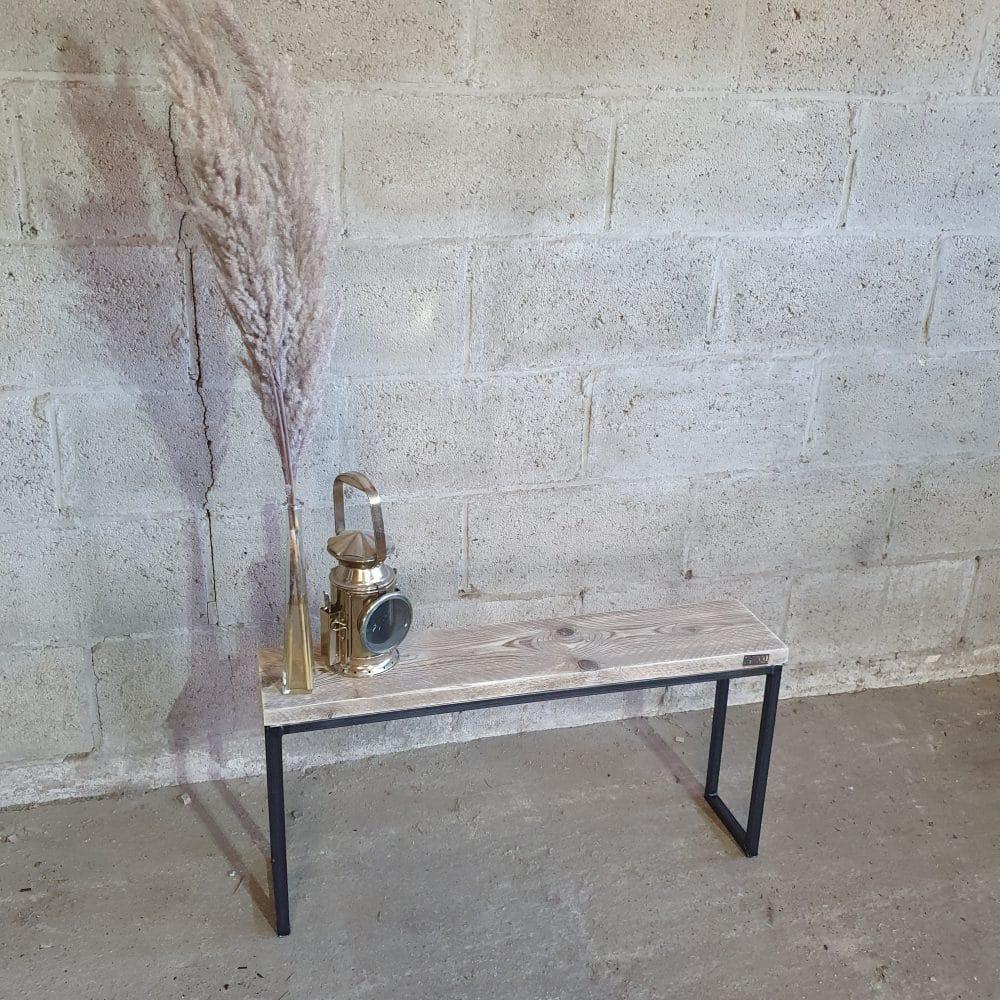 Een bankje dat je gebruikt als accessoire met daarop een spriet en een oude lamp.