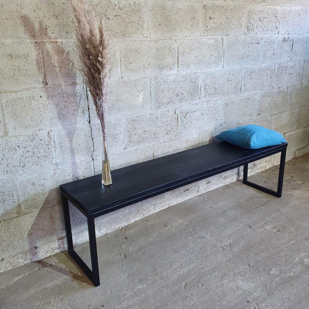 Zwart bankje met een stalen onderstel dat zwart is gepoedercoat, waarom een blauw kussentje ligt en een spriet staat ter decoratie.