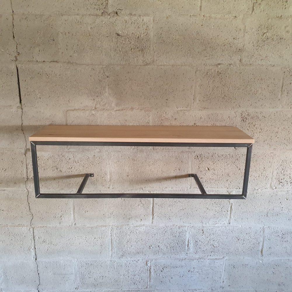 Onbehandeld staal, vastgemaakt aan een betonnen muur. Met erop een eikenhoutenplank. Resultaat is een industriële kapstok
