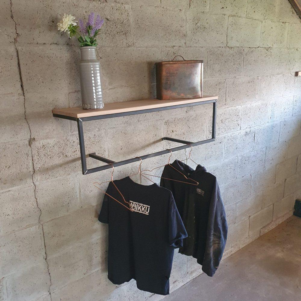 Op de werkplaats hang een kapstok aan de muur met daaraan 2 truien. Bovenop staat een vaas en een metalen blik