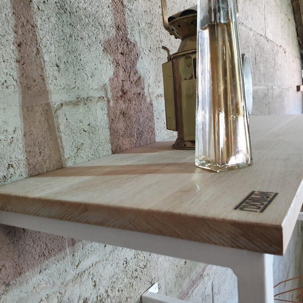 Close-up van het eikenhout dat bovenop een kapstok zit. Het frame is van wit metaal.