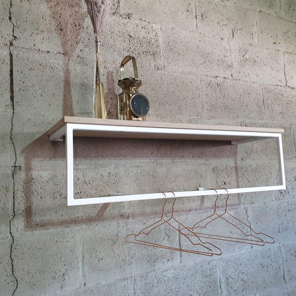 Kapstok bevestigd aan een stenen muur met een spriet op de hoedenplank.