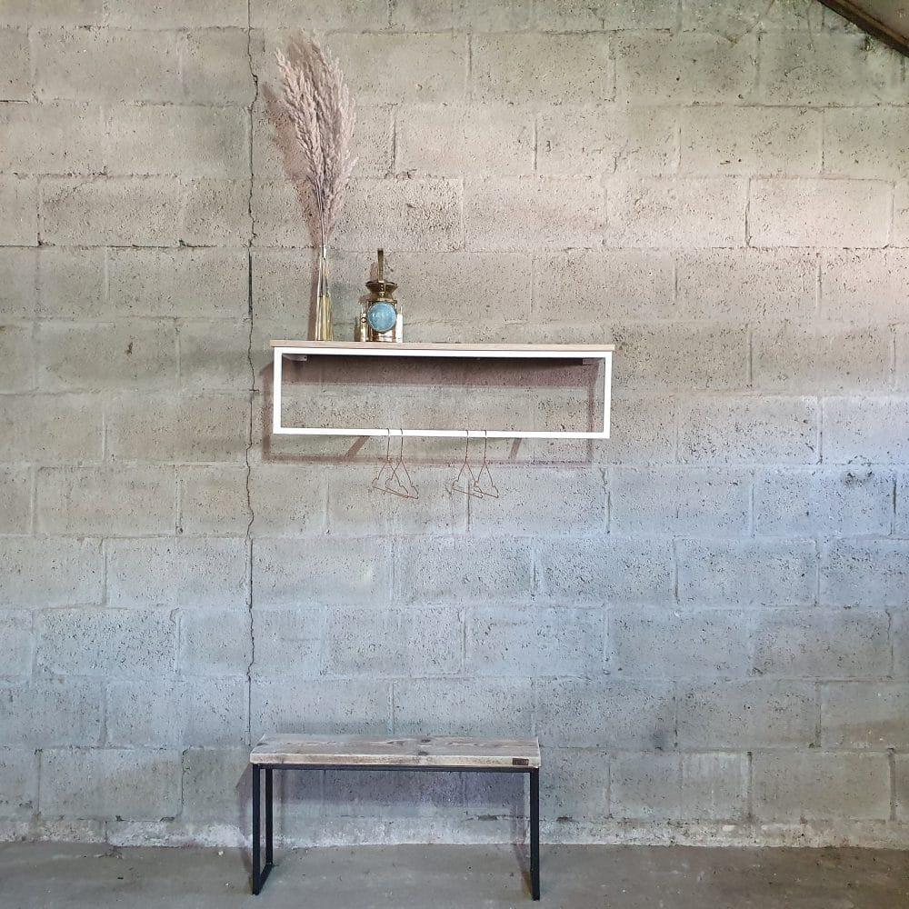 Overzichtsfoto van een witte kapstok met een houten hoedenplank. Daaronder staat een bankje van staal en hout.