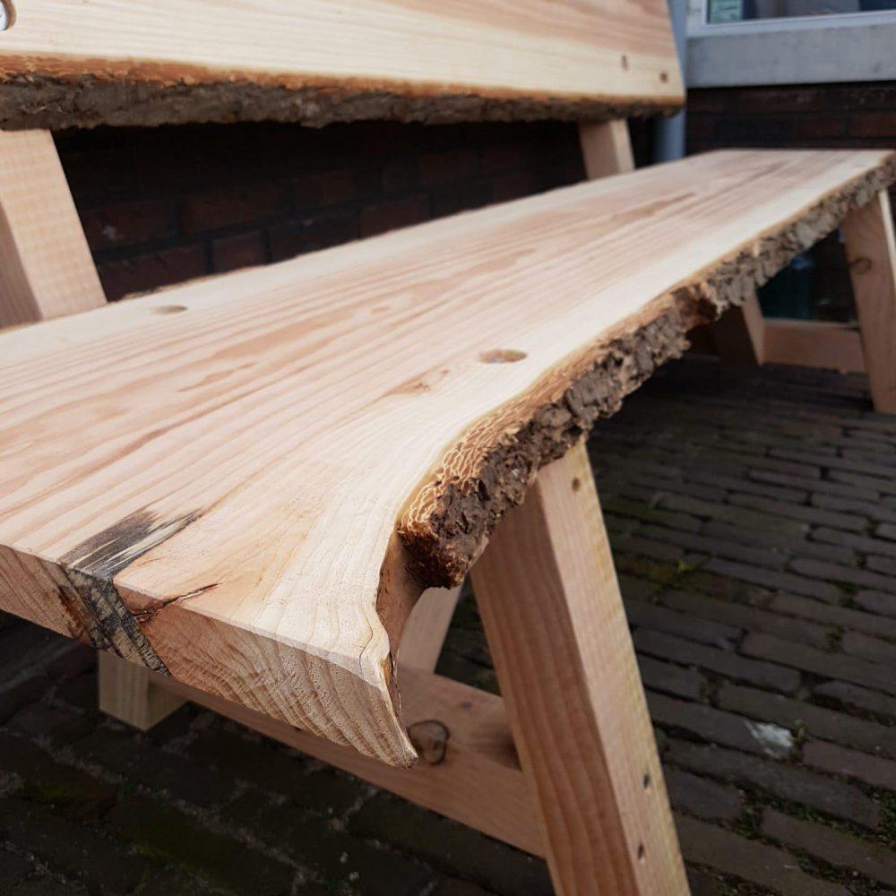 Bankje voor buiten van hout. Met een frame van hout en een zitgedeelte en rugdeel. Zitvalk lijkt een boomstam met boomschors.