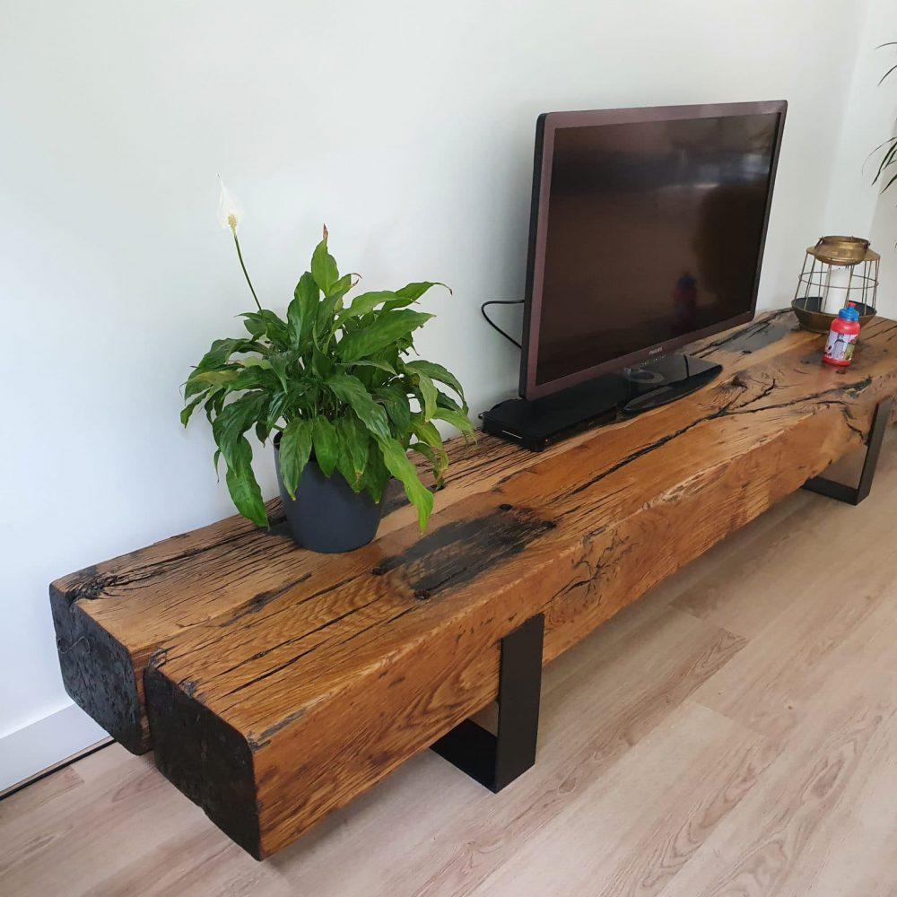 Tv-meubel met daarop een plantje, kaars en de televisie