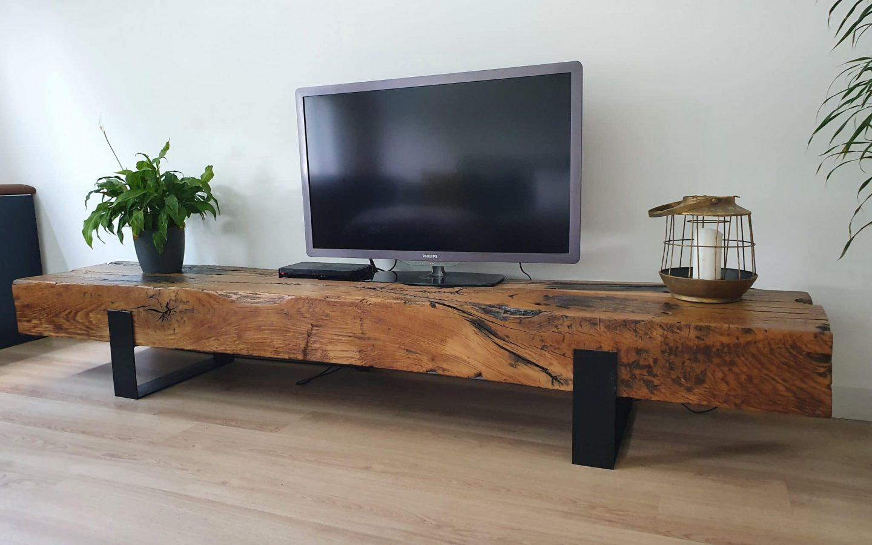 Warm bruin tv-meubel met zwarte poten. Meubel is massief en daarop staat een plant en een kaars als decoratie