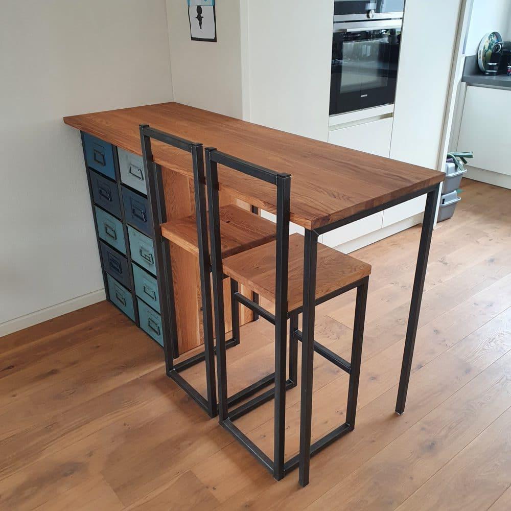 Hoge houten bartafel in een keuken met 2 barkrukken inclusief rugleuning en blauwgekleurde stalen bak verwerkt in de bar