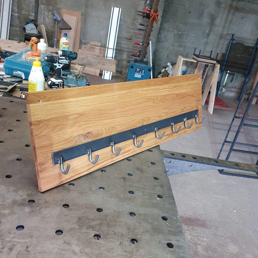 Een houten kapstok met daarop een stalen strip en 8 stalen haakjes, staat nu op de werkplaats maar komt aan de muur te hangen