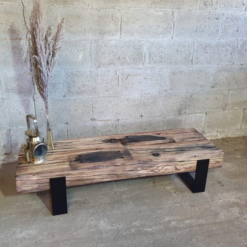 Tv-meubel gemaakt van hele dikke houten balken met daarop een spriet in een vaas en een oude mijnwerkers lamp