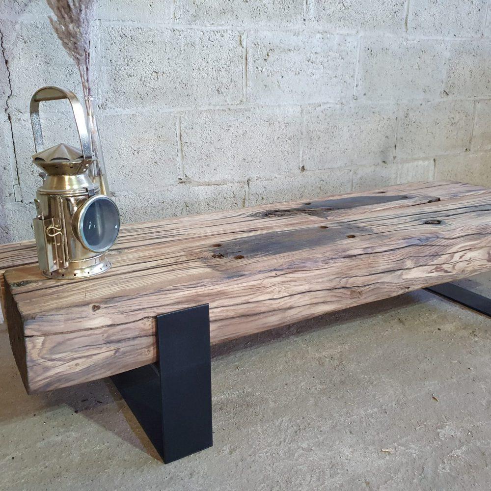Schuinvooraanzicht van een tv-meubel gemaakt van hout, spoorbielzen. Hele dikke oude eiken balken op een metalen onderstel. Erop staat een oude lamp en een vaasje met een spriet