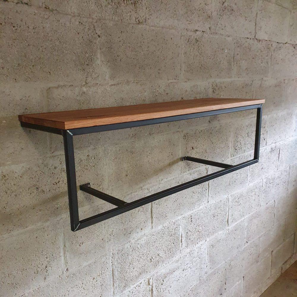 Een wand kapstok met een houten plank en daaronder een stalen, zwarte frame waar met 2 horizontale liggers aan de muur wordt gemonteerd. De jassen hangen je er met kleerhangers aan. Op maat te bestellen
