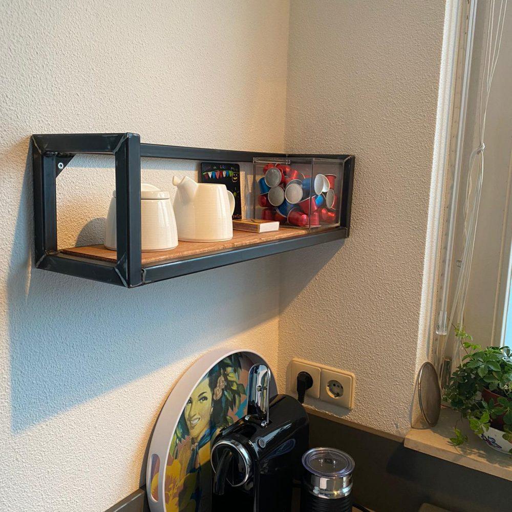 Hoek in de keuken met een plank aan de muur met een stoer stalen frame en daarop spulletjes die je in de keuken gebruikt