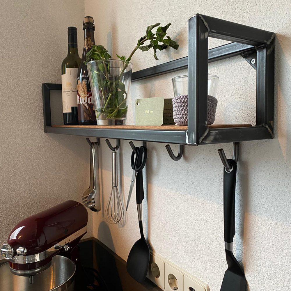 Multi-functionele plank in de keuken met wat haakjes voor keukenspulletjes en bovenop de plank staan accessoires en olijfolie
