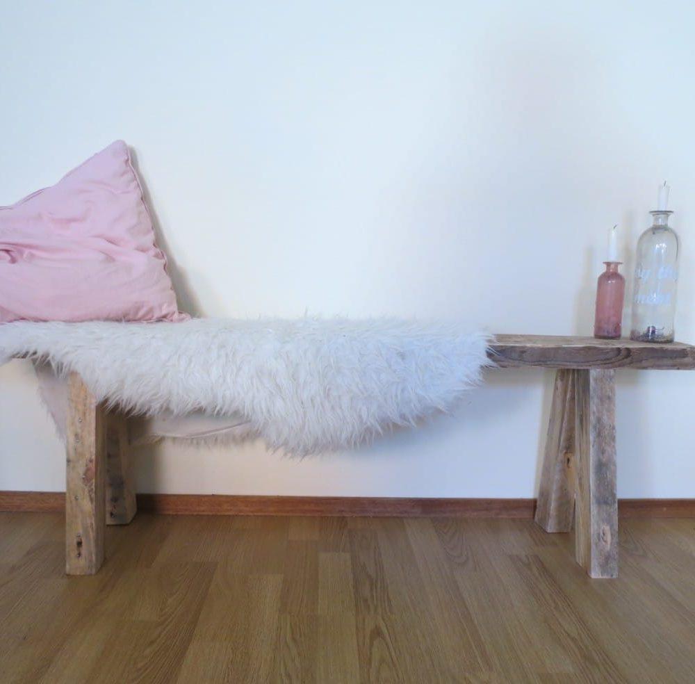 Houten bankje met daarop een wit schapenvelletje, een roze kussen en 2 kaarshouders