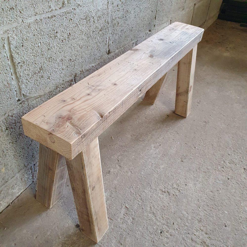 Details van een houten bankje met 4 poten en een dikke houten plank. Staat op de werkplaats voor een betonnen muur, op een betonnen vloer