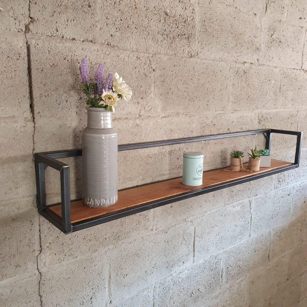 Wandmeubel met daarop een grijze vaas met een nepbloem en wat kleine kaarsen. Vastgemaakt aan een betonnen muur.