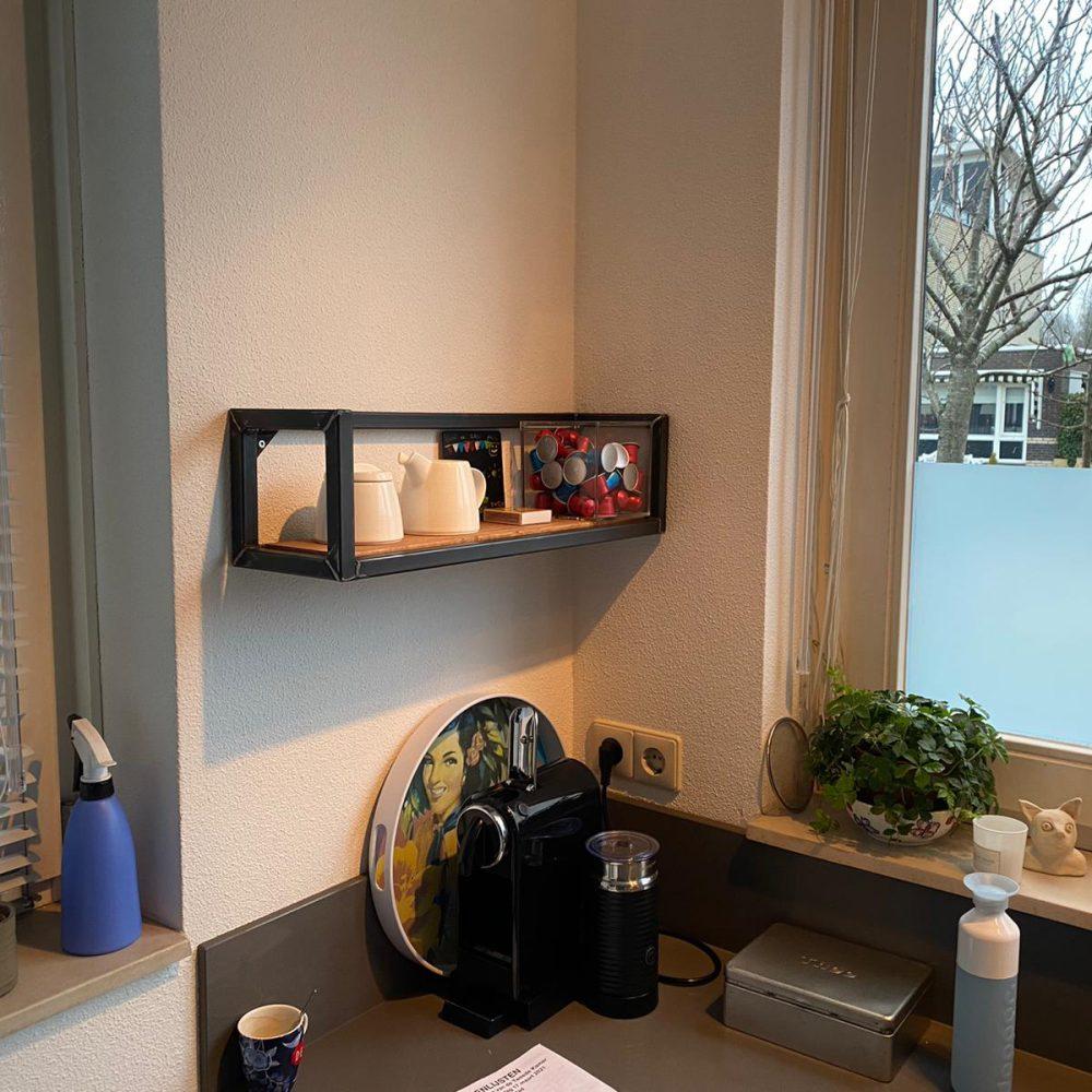 In een grijze keuken hangt aan de muur een plank met een stalen frame. Op de plank staat spulletjes om mee te koken