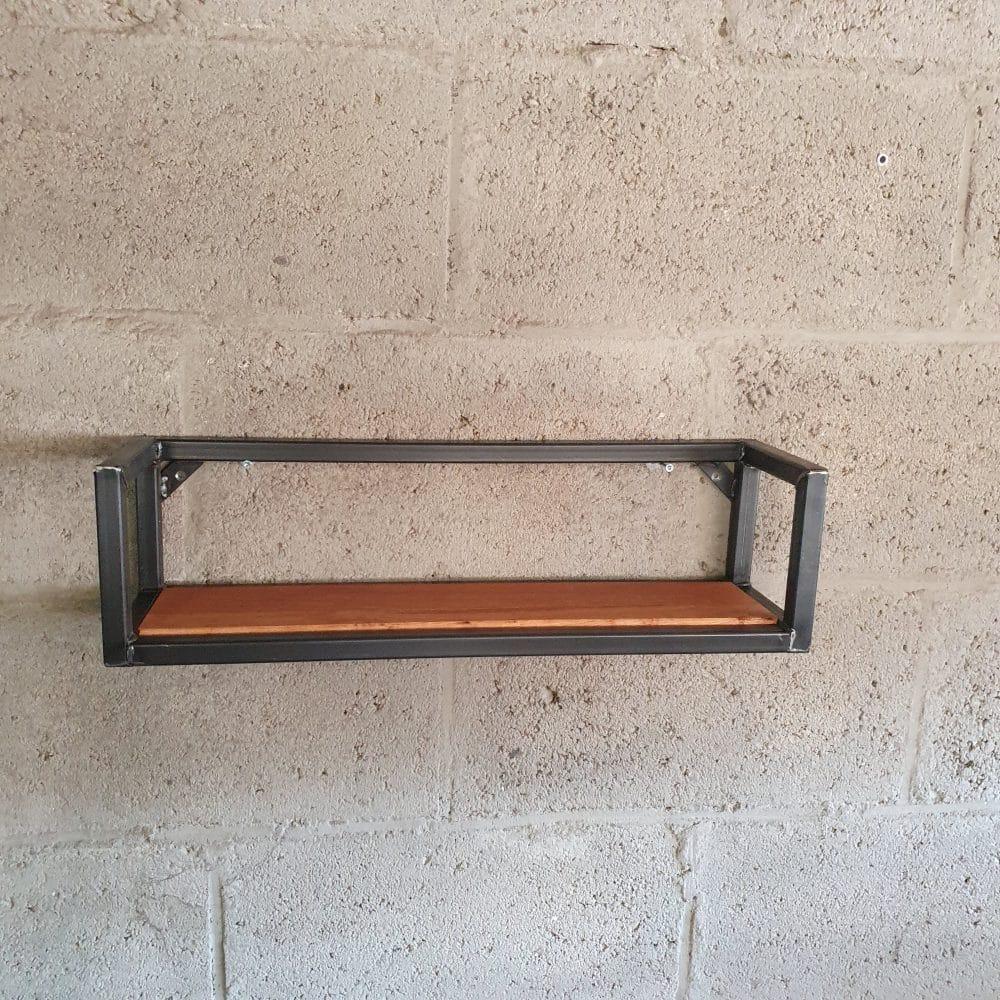 Industrieel meubel hangt aan de grijze muur. Zwart frame met een eiken plank erin