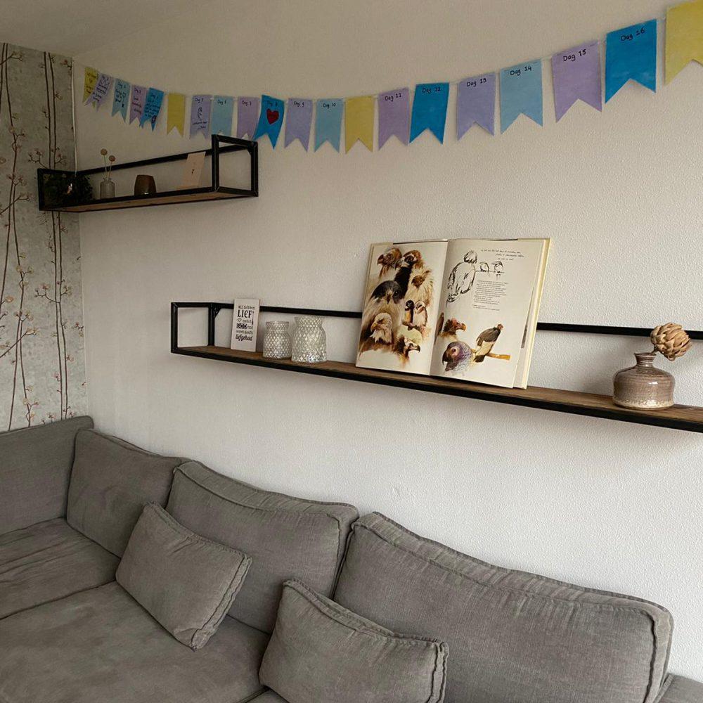 Woonkamer met een grijze bank, daarboven 2 wandrekken in 2 verschillende afmetingen met allemaal accessoires erop. Ook een gekleurde slinger hangt aan de muur.