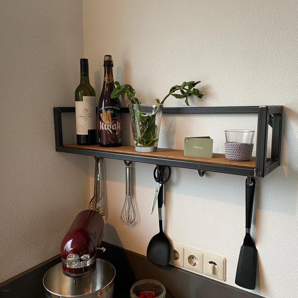 Keukenplank met daarop olijfolie en kaarsjes. Onder de plank hangen spulletjes voor in de keuken en om het hout zit een stalen frame