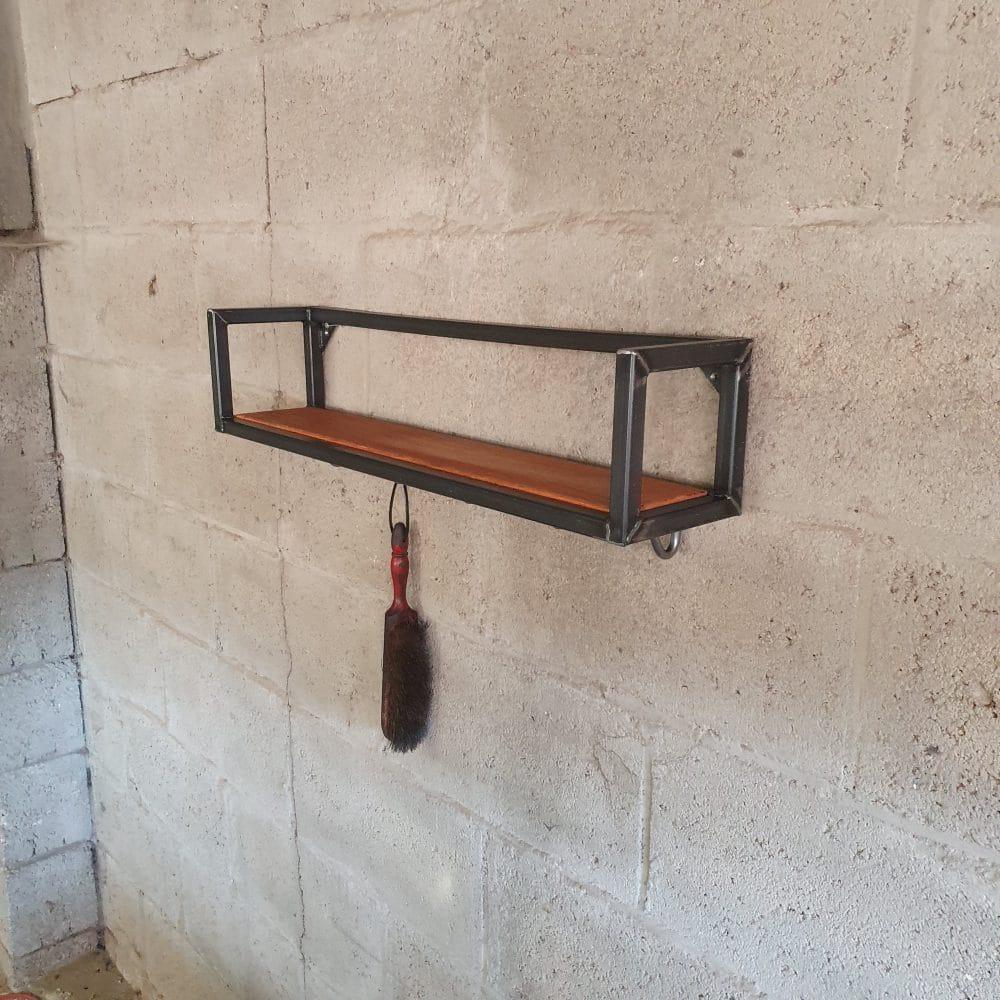 Plank bevestigd aan een stenen muur. Om de plank zit een stalen frame en aan één van de haakjes onder de plank hangt vegertje