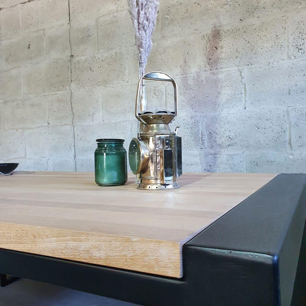 Close-up van een houten tafel gemaakt van eikenhout in een stalen frame. Op de tafel staat een mijnwerkers lamp een groene kaars en een spriet in een vaasje