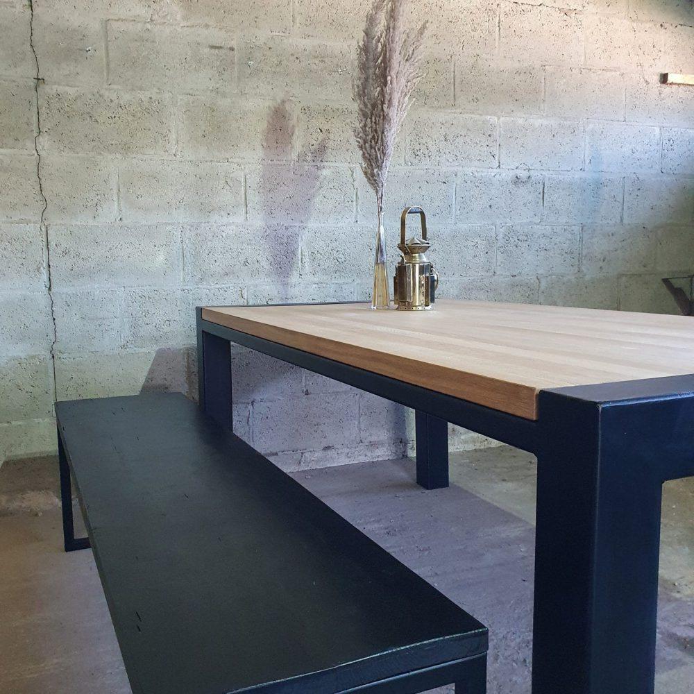 Zijaanzicht tafel met een zwarte bank ernaast. Tafel is van 4cm massief eikenhout gemaakt en in een zwart metalen frame geplaatst