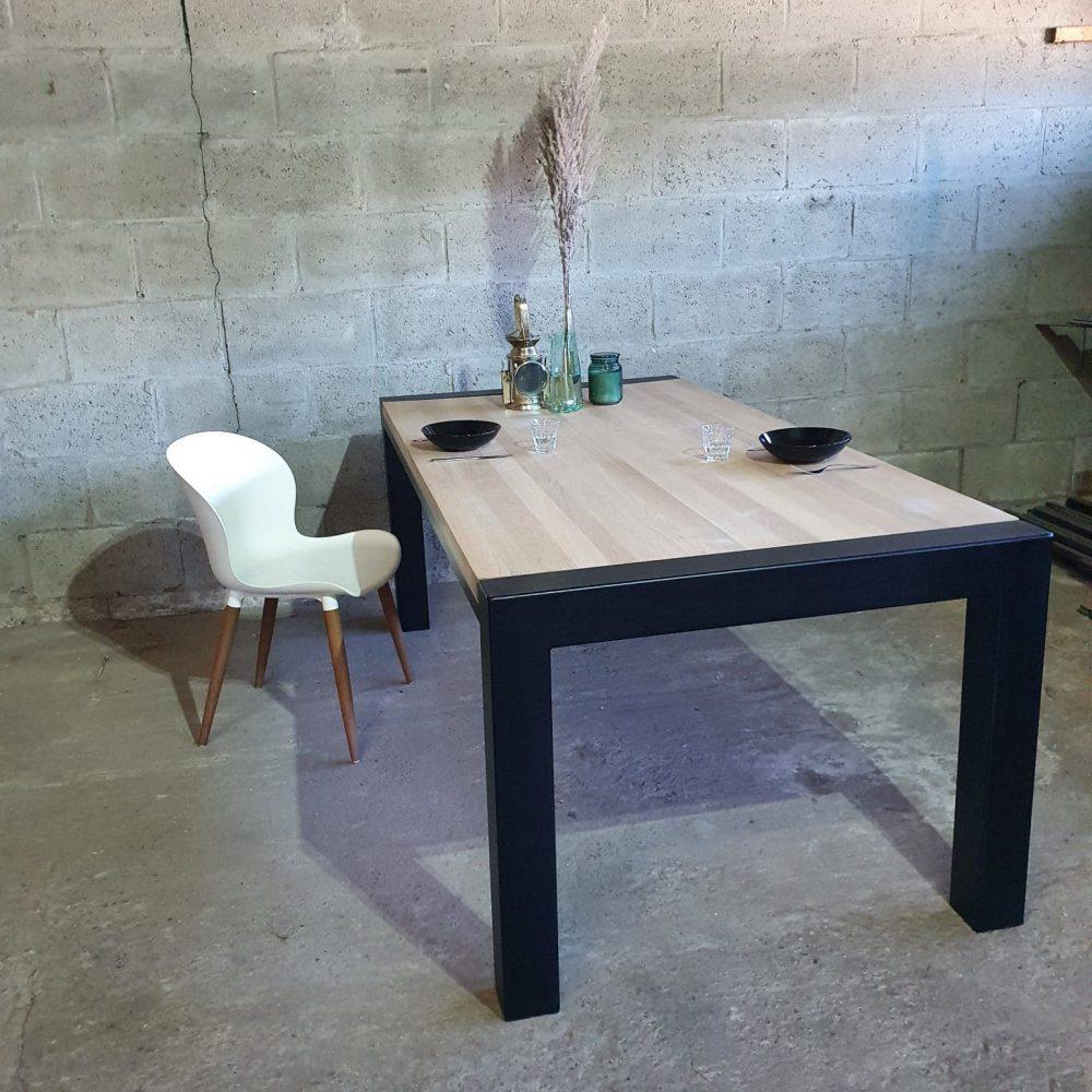 Eikenhouten eettafel met een stalen frame en een massief eikenblad van 200 cm lang bij 100 cm breed, daarnaast een witte stoel en 2 bordjes op de tafel