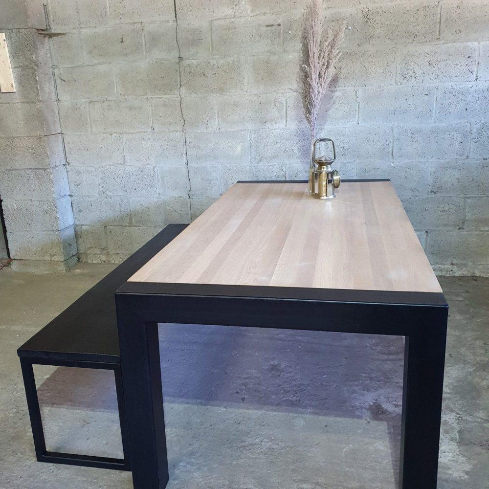 Aanzicht vanaf de zijkant van een eikenhouten tafel met daaraan een zwart bankje. Beide gemaakt van staal en hout. Op de tafel staat een spriet en een oude mijnwerkers lamp ter decoratie