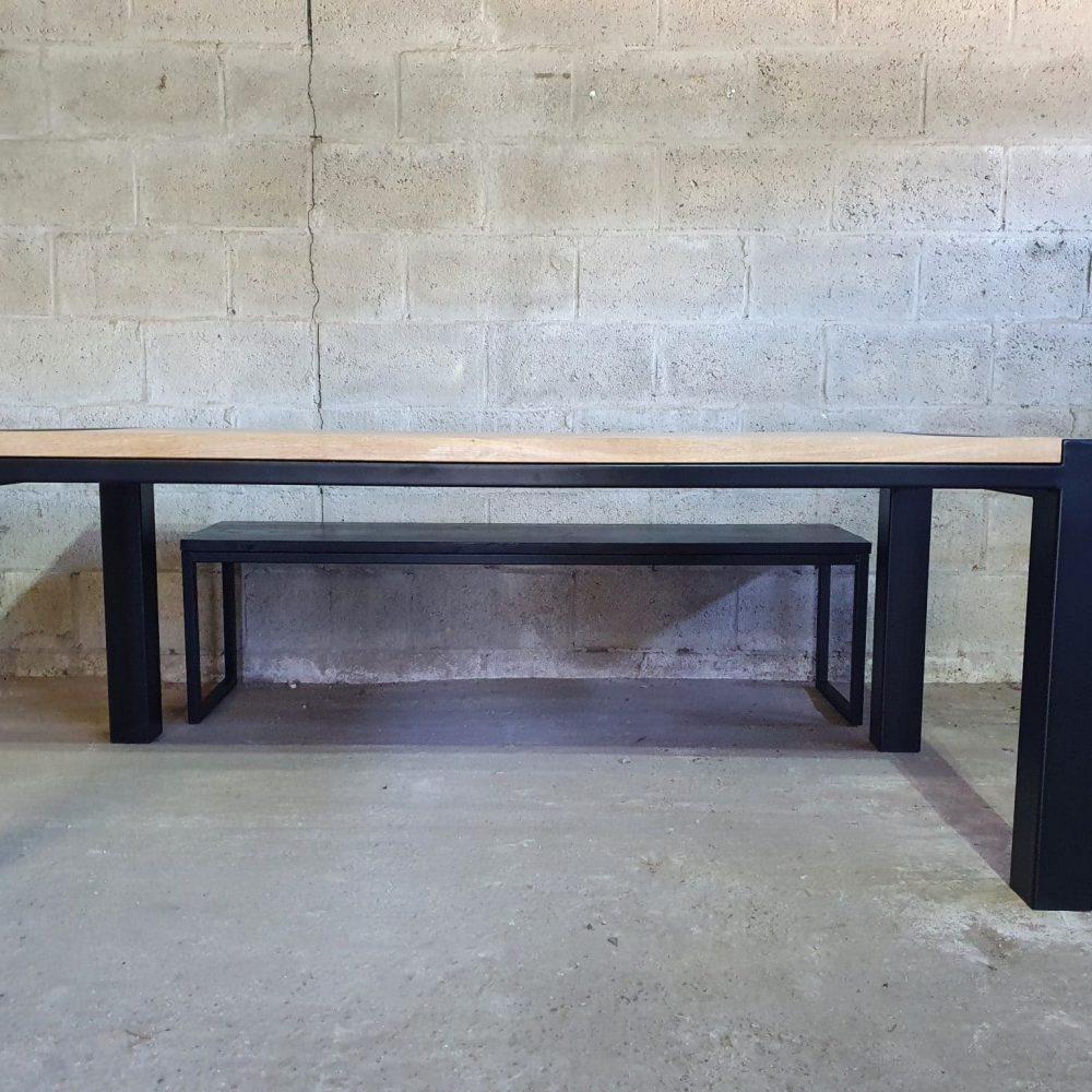 Vooraanzicht van een tafel die op een werkplaats staat. Een betonnen vloer met grove muur op de achtergrond. Achter de tafel staat een zwart bankje. Ook gemaakt van staal en hout.
