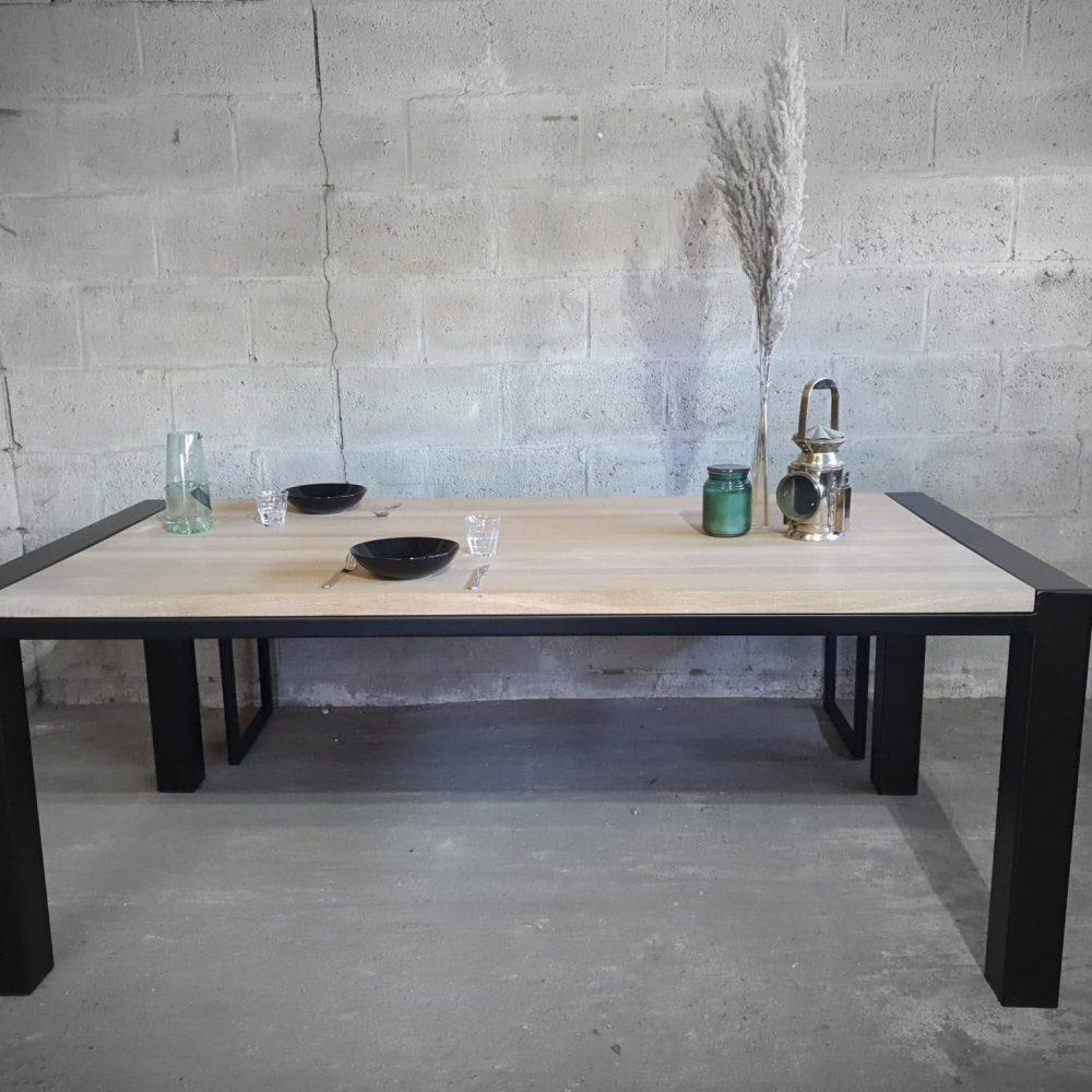 Vooraanzicht eikenhouten tafel 200x100. Een zwart frame met daarop een gewhitewashed blad waarop 2 zwarte borden staan en wat prullaria.