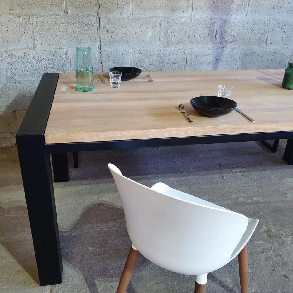 Sfeerbeeld van een eettafel met daarop 2 zwarte bordjes, glaasjes en een blauwe karaf. Tafel is gewhitewashed eiken, met mat zwarte stalen poten