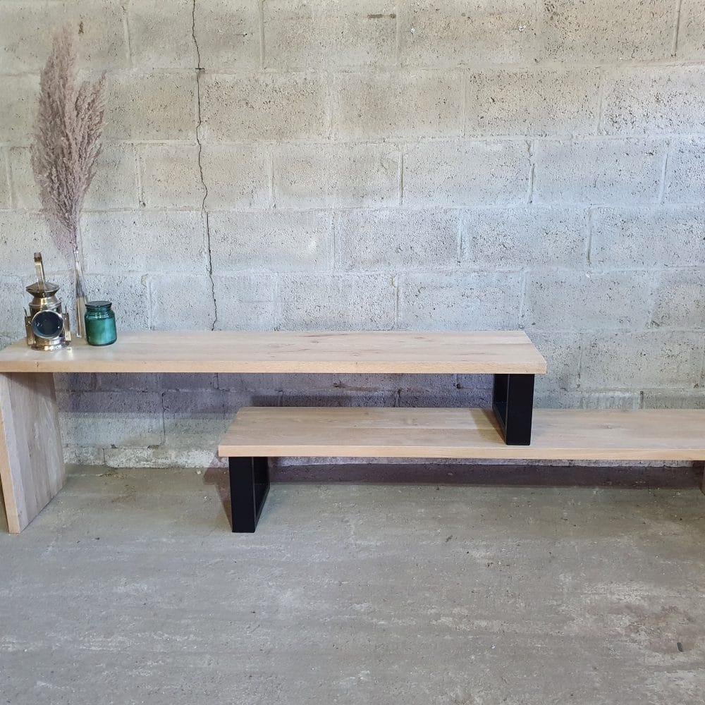 Vooraanzicht van een tv-meubel, waarbij 2 delen op elkaar staan. Links en rechts is de poot van hout, in het midden staan 2 zwarte metalen poten.