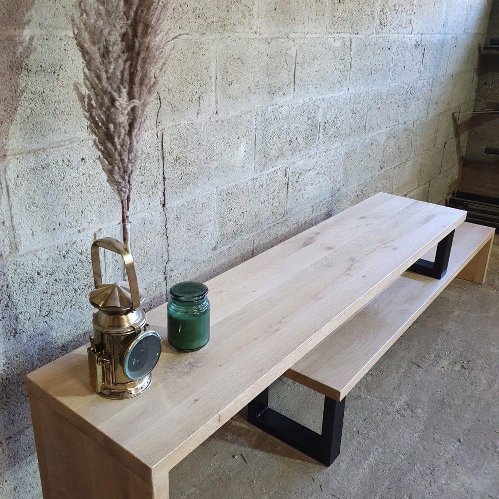 Sfeerbeeld van een tv-meubel van eikenhout waarop 3 accessoires staan. Hout wordt gecombineerd met zwarte stalen poten.