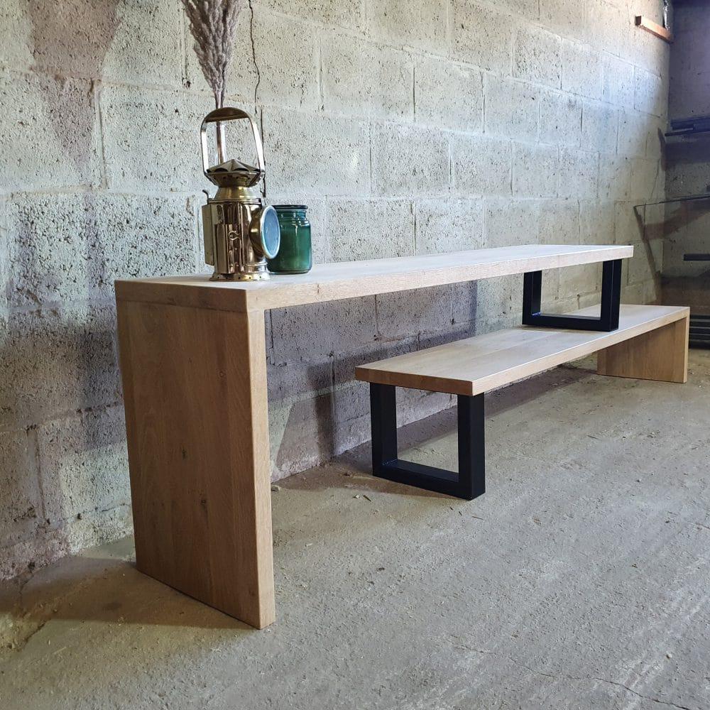 Tv-meubel van licht eikenhouten bestaande uit 2 onderdelen die op elkaar geplaatst zijn. Daarmee kan je de lengte van het meubel zelf bepalen. Op het tv-meubel staat een oude mijnwerkerslamp, een kaarsje en een vaasje met spriet.