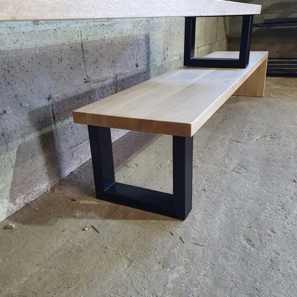 Close-up foto van een tv-meubel waarbij het het massieve eikenhout van 4 cm gecombineerd met u-poten van zwart staal