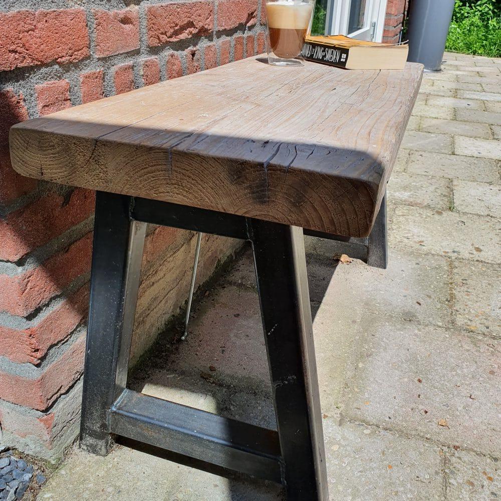 Zij-aanzicht van een hout en staal bankje. Voor een huis op een tegel vloer,