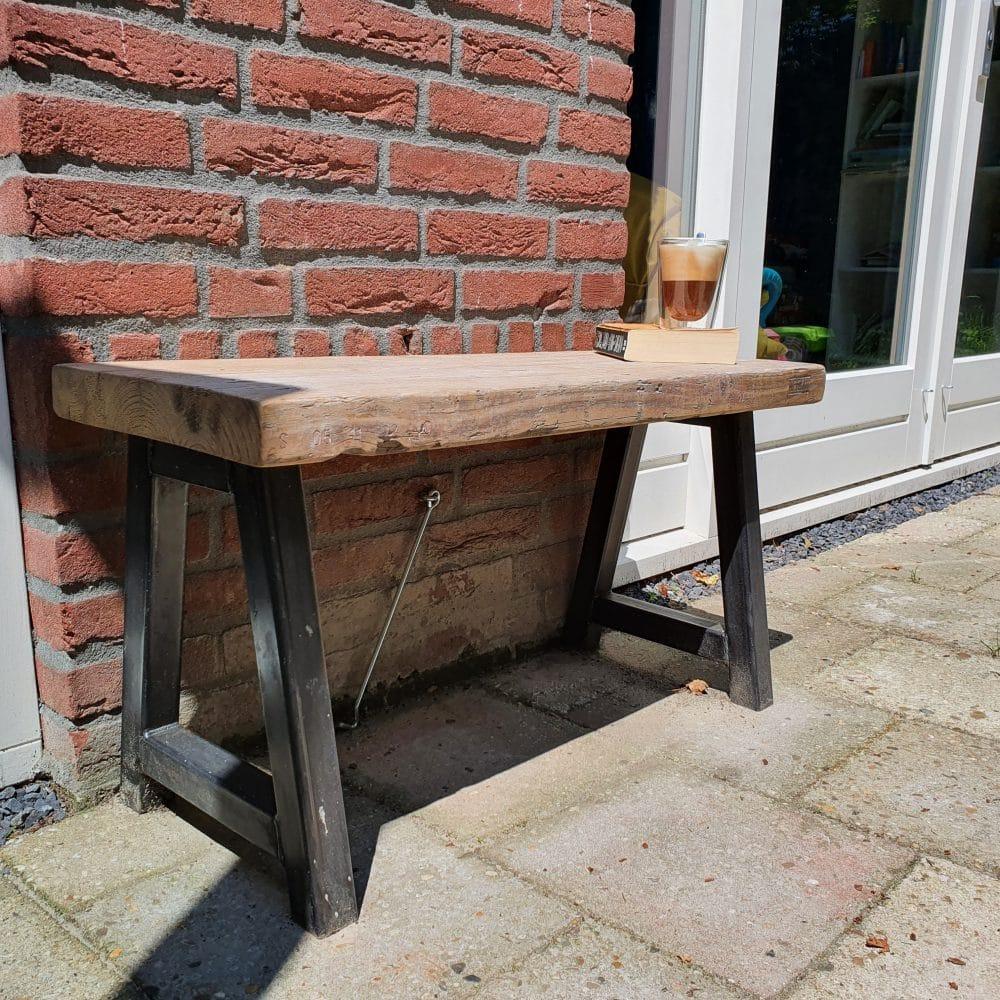 Schuinvoor aanzicht van een staal en houten bankje, sfeerbeeld met een cappucino en een boekje in het zonnetje