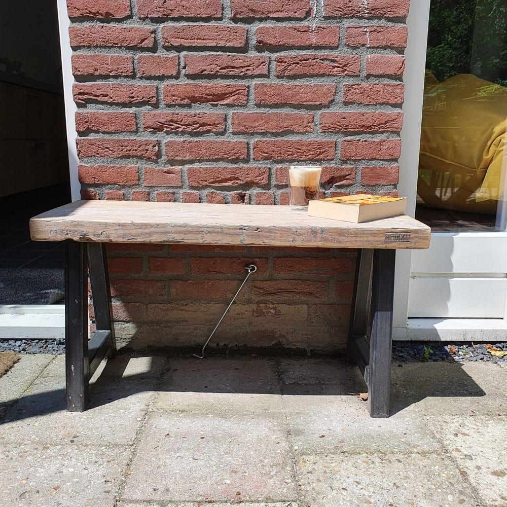 Vooraanzicht van een bankje in de zon voor een huis.