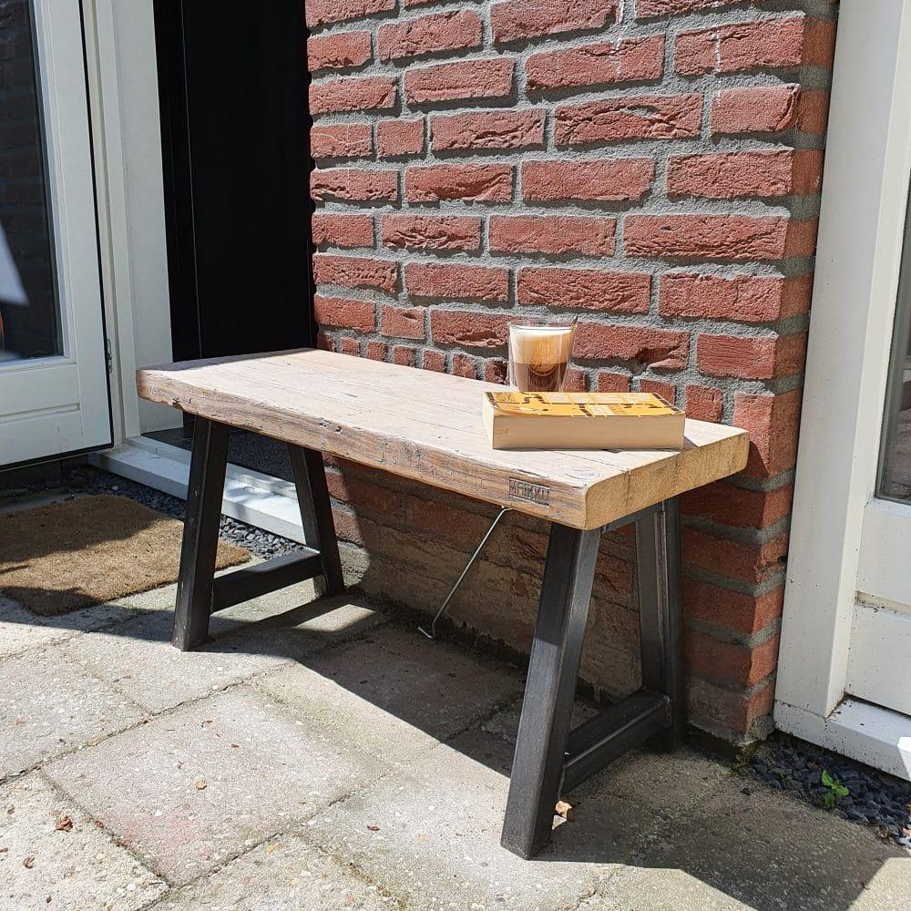 Rechtsvoor aanzicht van een bankje gemaakt van hout en staal. Voor een huis met een rode muur en op de grond liggen grijze tuintegels