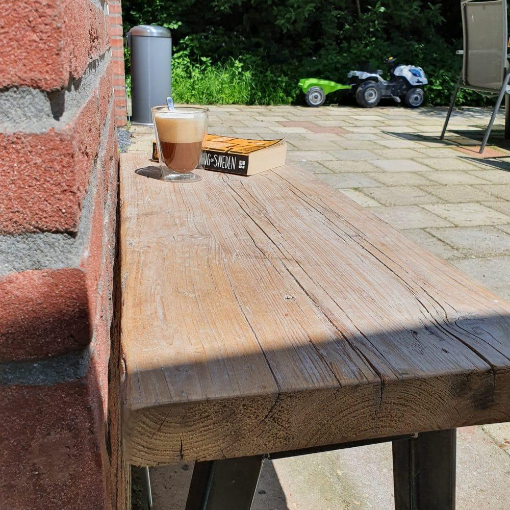 Close-up van een houten bankje in de zon. Daarop ligt een boek en staat een glas cappucino.