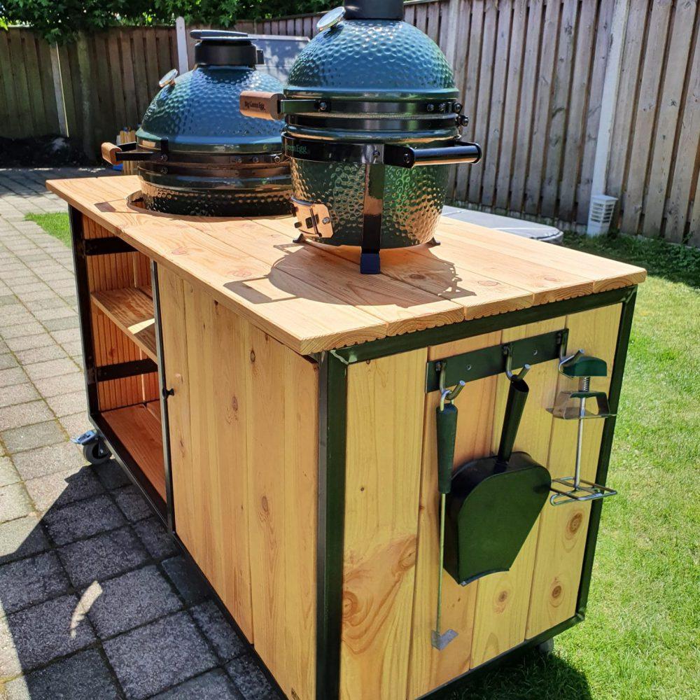 Bbq tafel op wielen, foto van de zijkant. Kleine green egg bbq op de tafel en een grote green egg in gebouwd. Vurenhout met staal