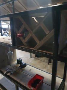 Wijnrek als onderdeel van een grote industriële maatwerk kast. Vierkant vak bestaande uit een aantal schuine vakken.