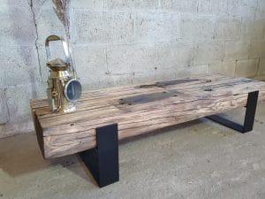 Industrieel tv-meubel met een zwarte poot en daarop een spoorbielzen balk.