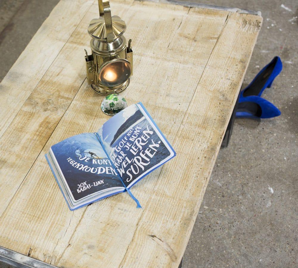 Stoere salontafel gemaakt van een steenschot en een metalen onderstel. Op de tafel ligt een boekje en staat een oude mijnwerkerslamp.